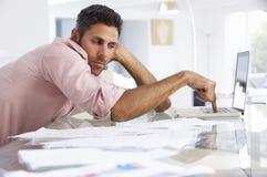 Homme soumis à une contrainte travaillant à l'ordinateur portable dans le siège social Image stock