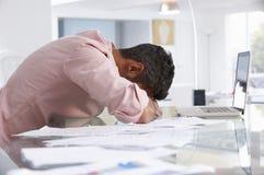 Homme soumis à une contrainte travaillant à l'ordinateur portable dans le siège social Images stock