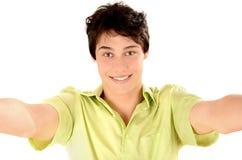Homme souriant avec des mains atteignant  Jeune homme heureux prenant une photo de selfie Photographie stock libre de droits