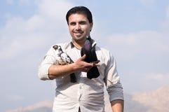 Homme souriant avec des pigeons Photographie stock libre de droits