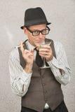Homme souriant d'un air affecté sirotant Martini Image stock