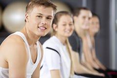 Homme souriant tout en se reposant avec des amis dans le gymnase Photos libres de droits