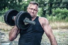Homme sportif établissant avec une haltère devant le gymnase de rue Force et motivation S?ance d'entra?nement ext?rieure Exercice images stock