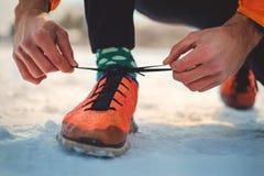 Homme sportif attachant une espadrille droite sur une terre neigeuse Photos stock