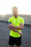 Homme sportif bel écoutant la musique dans des écouteurs Photo stock