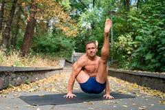 Homme sportif bel faisant des asanas de yoga en parc Images stock
