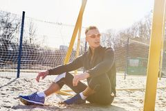 Homme sportif bel s'asseyant sur le gisement de sable pour le football de plage image stock