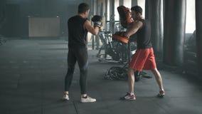 Homme sportif combattant pendant la formation avec l'entraîneur de boxe au gymnase mouvement 4k lent banque de vidéos