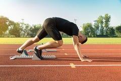 Homme sportif commençant pulser dans des rayons du soleil photographie stock