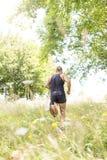 Homme sportif courant en bas du champ par jour ensoleillé photo libre de droits