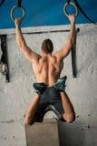 Homme sportif d'exercice de muscle- faisant la séance d'entraînement intense au gymnase sur les anneaux gymnastiques photographie stock libre de droits