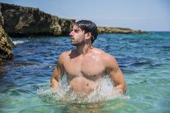 Homme sportif dans la mer ou l'océan sautant vers le haut de l'émergence Photo libre de droits