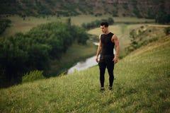 Homme sportif dans la séance d'entraînement de vêtements de sport dehors, d'isolement sur un beau fond de paysage image libre de droits