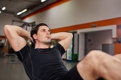 Homme sportif dans le sportwear noir fonctionnant avec le sien abdominal sur le simulateur dans le gymnase photos stock