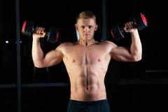 Homme sportif de puissance belle avec l'haltère regardant avec confiance en avant Bodybuilder fort six paquets, ABS parfait image libre de droits