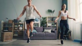 Homme sportif et femme des jeunes faisant la corde à sauter de sports ensemble dans l'appartement clips vidéos