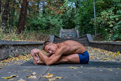 Homme sportif faisant des asanas de yoga en parc Photographie stock libre de droits