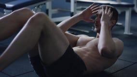 Homme sportif faisant l'exercice de bicyclette dans un gymnase banque de vidéos