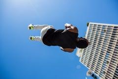 Homme sportif faisant le saut périlleux arrière dans la ville photos stock