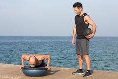 Homme sportif faisant un exercice de pompe avec l'entraîneur sur la plate-forme d'équilibre images libres de droits