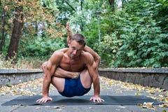 Homme sportif flexible bel faisant des asanas de yoga en parc Photos stock