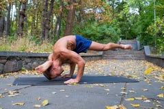 Homme sportif flexible bel faisant des asanas de yoga en parc Photographie stock libre de droits