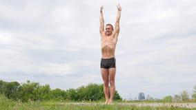 Homme sportif flexible bel faisant des asanas de yoga en parc banque de vidéos