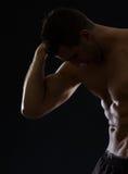 Homme sportif intense posant sur le noir photographie stock