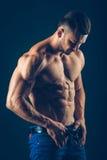 Homme sportif intense sur le fond noir À la pompe photo stock