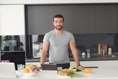 Homme sportif posant dans la cuisine Avant lui sur la table sont les divers légumes et fruits Images libres de droits