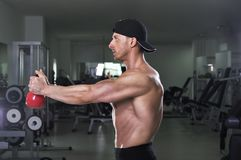 Homme sportif puissant bel faisant l'exercice d'épaule avec la cloche de bouilloire image libre de droits
