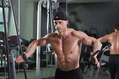 Homme sportif puissant bel faisant l'exercice de croisement de câble image stock