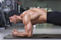 Homme sportif puissant bel faisant l'exercice de planche images stock