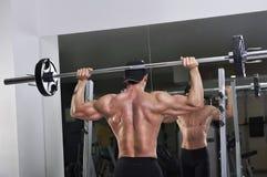 Homme sportif puissant bel faisant l'exercice de presse d'épaule de barbell image stock