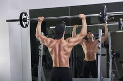 Homme sportif puissant bel faisant la presse d'épaule de barbell photo stock