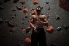 Homme sportif utilisant la craie avant de s'élever dans un gymnase bouldering photo libre de droits