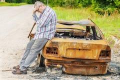 Homme stressant sur brûlé en bas de l'épave de voiture du côté de la route Images stock