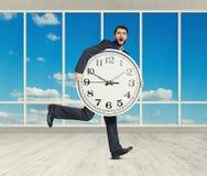 Homme stupéfait avec la grande horloge blanche Photographie stock libre de droits