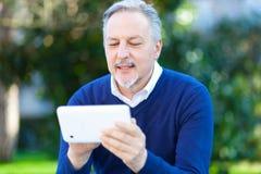 Homme supérieur à l'aide d'un comprimé numérique extérieur Photo libre de droits