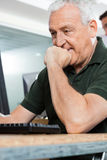 Homme supérieur à l'aide de l'ordinateur dans la salle de classe Image stock