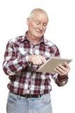 Homme supérieur à l'aide de l'ordinateur de comprimé semblant confus Photographie stock libre de droits