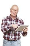 Homme supérieur à l'aide de l'ordinateur de comprimé semblant confus Photographie stock