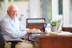 Homme supérieur à l'aide de l'ordinateur portable sur le bureau à la maison Image stock