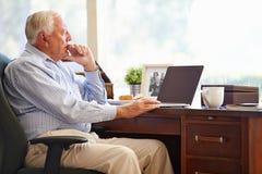 Homme supérieur à l'aide de l'ordinateur portable sur le bureau à la maison Photos libres de droits