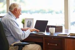 Homme supérieur à l'aide de l'ordinateur portable sur le bureau à la maison Photos stock