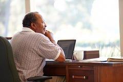 Homme supérieur à l'aide de l'ordinateur portable sur le bureau à la maison Photographie stock
