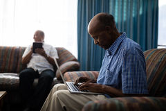Homme supérieur à l'aide de l'ordinateur portable tout en se reposant sur le sofa Photographie stock