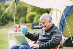 Homme supérieur à l'aide de l'ordinateur portable au terrain de camping Images stock