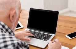 Homme supérieur à l'aide de l'ordinateur portable avec la maquette d'écran vide Image stock