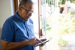 Homme supérieur à l'aide du comprimé numérique à la maison de repos Image stock